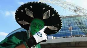A fan poses outside the stadium before the