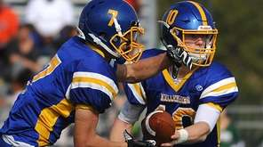 Matthew Sluka, Kellenberg quarterback, right, hands off to