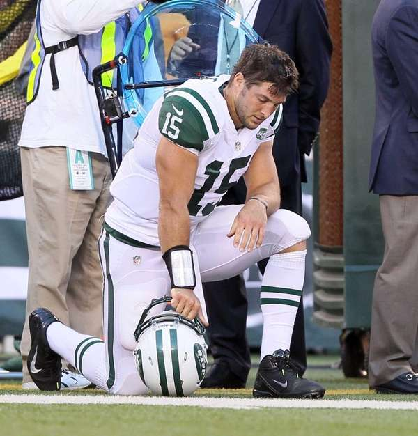Tim Tebow kneels before the start of a