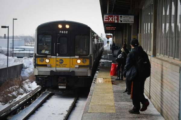 Passengers wait for an arriving train at the