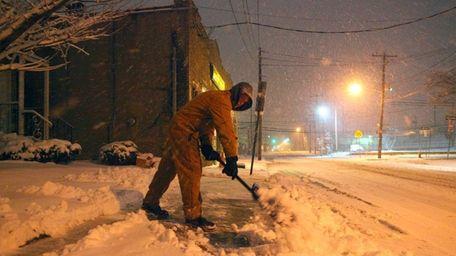 Kevin Nicoll shovels his walkway on Willis Avenue