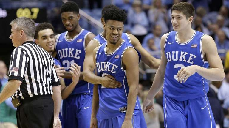 Duke's Quinn Cook, center, celebrates with teammates following