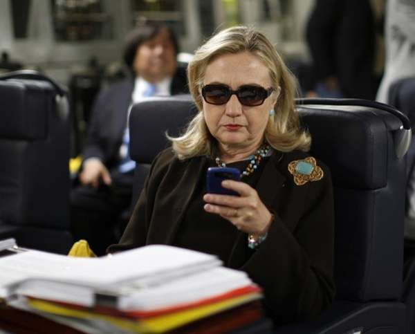 Then-Secretary of State Hillary Rodham Clinton checks her