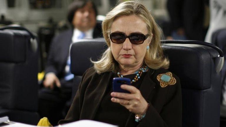 Then-Secretary of State Hillary Rodham Clinton checks her