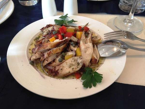 Grilled octopus is garnished with capers, peppers and