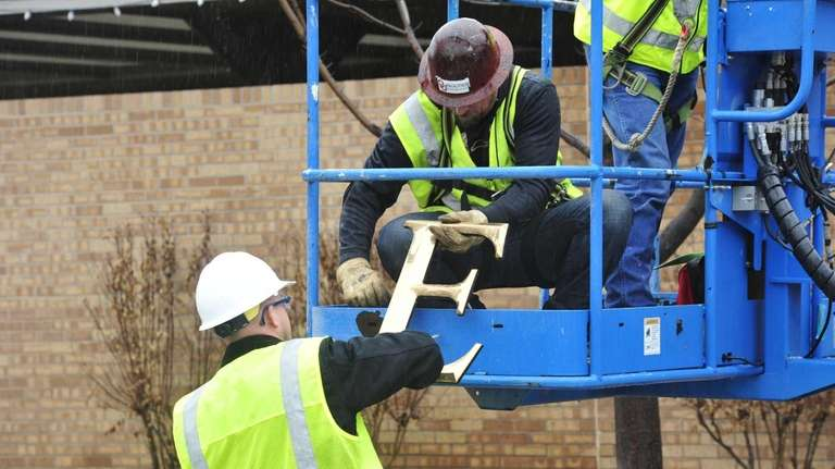 Facility workers remove sign lettering from the Sigma