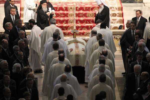 Members of the clergy touch the casket of