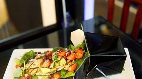 Spinach and pomegranate salad with chicken is served