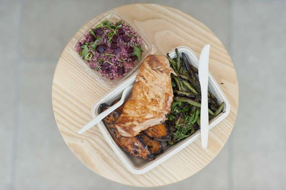Grilled salmon is served with charred kale, charred