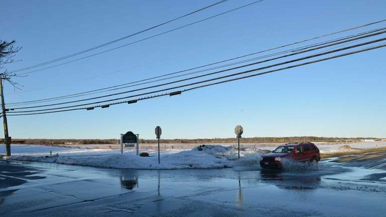 Snow melt water trickles across the street at