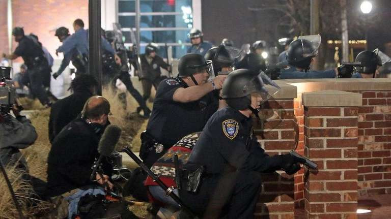 Police take cover after two officers were shot
