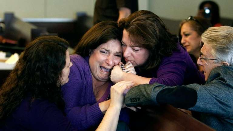 Christine Perolini, second from left, is comforted by