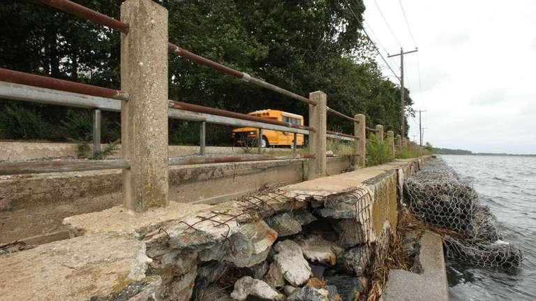 A school bus passes a Sandy-damaged section of