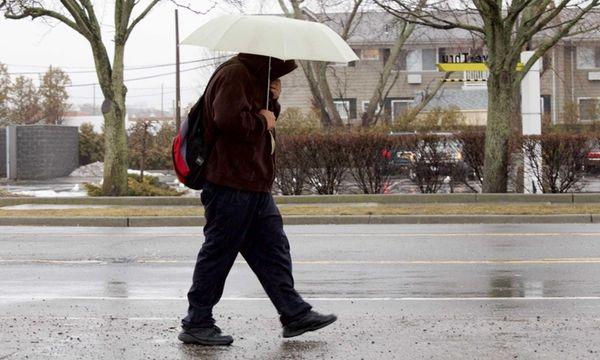 A man walks in the rain in Islip