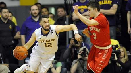 Stony Brook's Kameron Mitchell defends against Albany's Peter