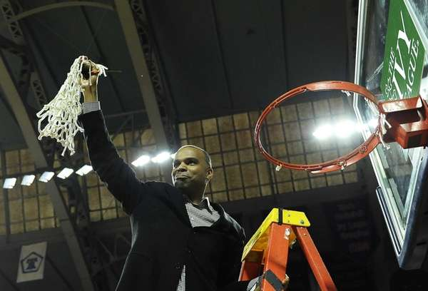 Harvard head coach Tommy Amaker cuts down the