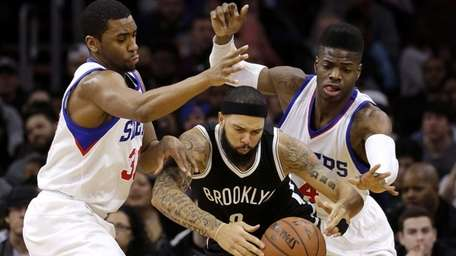Brooklyn Nets' Deron Williams, center, tries to hang