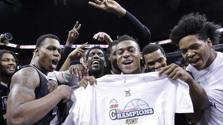 VCU guard Melvin Johnson holds up a championship