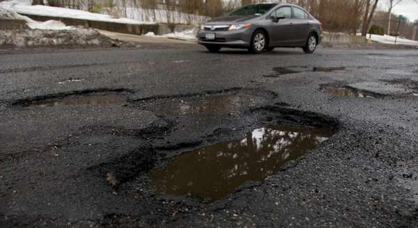 A car passes large potholes on a Long