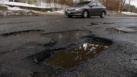 A car passes large potholes on a Long
