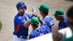 Mets catcher Kevin Plawecki, left, is greeted at