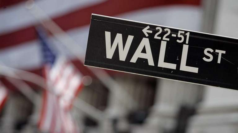 A Wall Street sign near the flag-draped facade