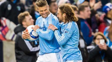 Defender Chris Wingert, left, celebrates with midfielder Ned