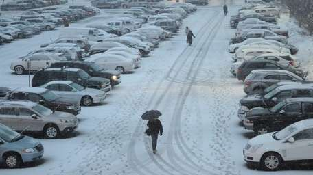 Commuters walk in the parking lot of the