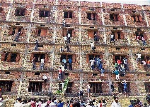 Indians climb the wall of a building to
