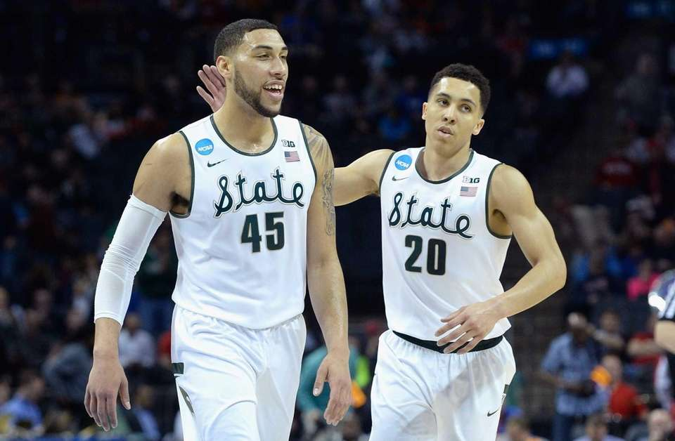 Teammates Denzel Valentine #45 and Travis Trice #20