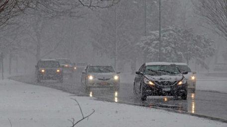 Cars drive through a snowy Eisenhower Park on