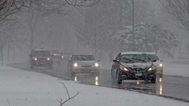 Cars drive through a snowy Eisenhower Park on