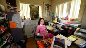 Yanira Chacon-Lopez sits in her Westbury office surrounded