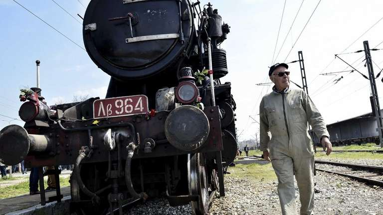A Hellenic Railway officer walks in front of