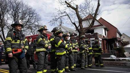 Firefighters stand in front of the House fire