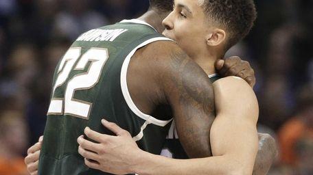 Michigan State's Branden Dawson, left, hugs Travis Trice,