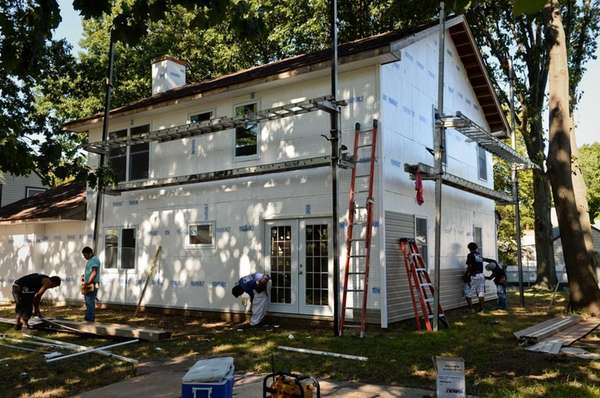 Workers from Allied Improvements place siding onto the