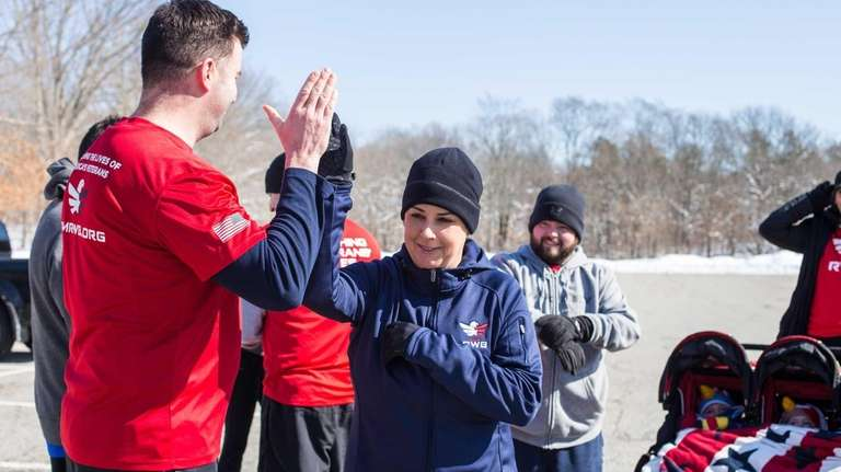 Team RWB social director Alina Perez, center, high-fives