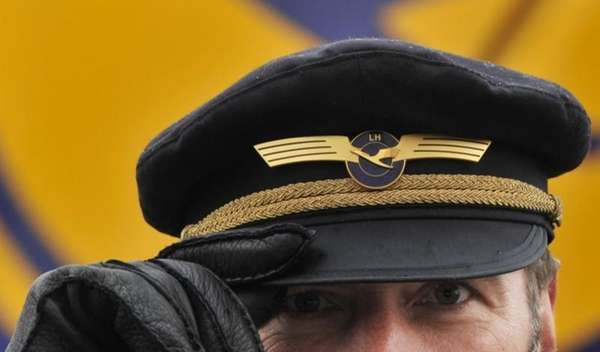 A Lufthansa Airlines pilot holds the brim of