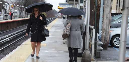 Commuters dodge raindrops at the LIRR station on