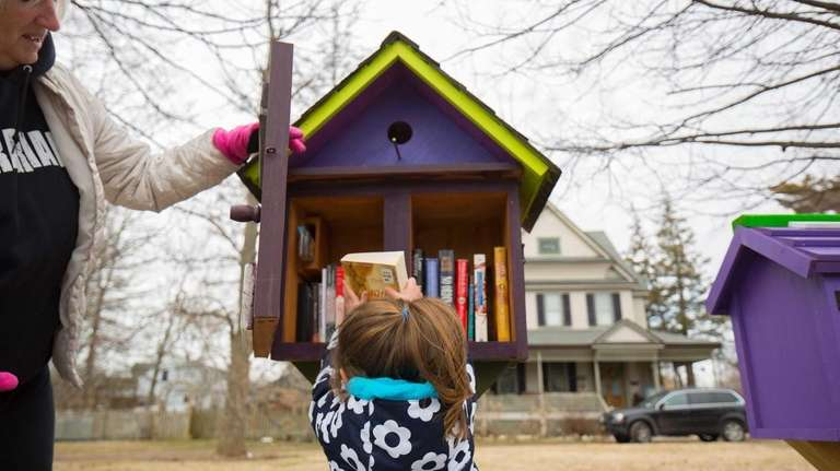 Lucy Fiddler, 3, takes a book from a