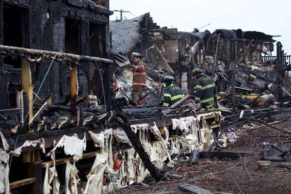 Firefighters survey the damage after a fire in