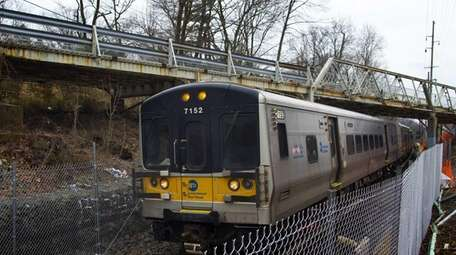A train passes under the Colonial Road bridge