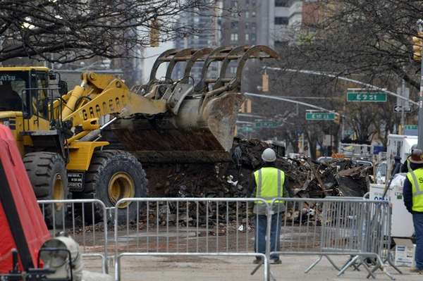 A bulldozer pushes away debris in front of