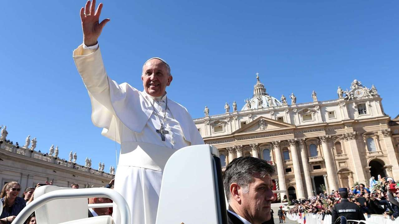 Pope Francis waves to the faithful as he