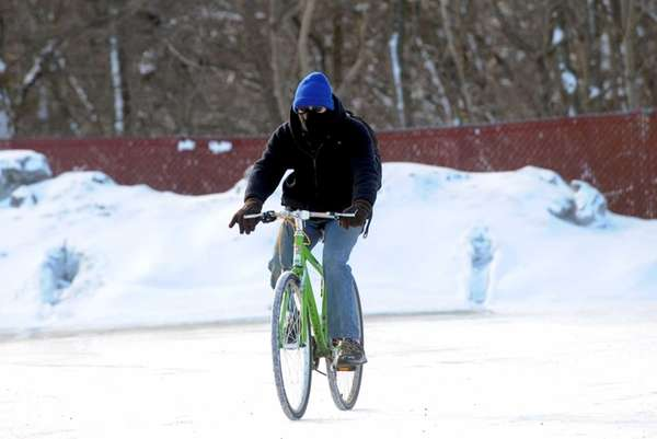 A bicyclist rides along snow-covered Mill Road in
