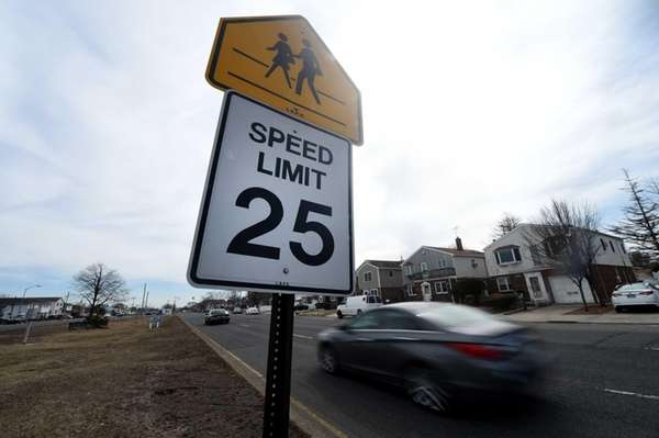 A new 25 mph speed limit sign sits