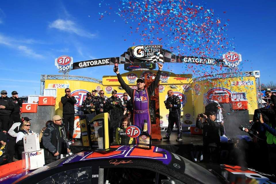 Denny Hamlin celebrates in Victory Lane after winning