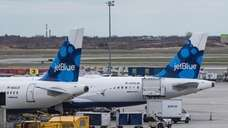 JetBlue planes sit at their gates at John