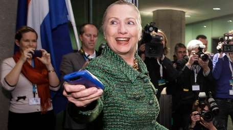 Then-U.S. Secretary of State Hillary Rodham Clinton hands